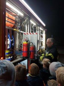 Ein Feuerwehrmann zeigt den Interessierten Kindern den Inhalt eines Einsatzfahrzeuges und erklärt wofür die einzelnen Geräte gedacht sind.